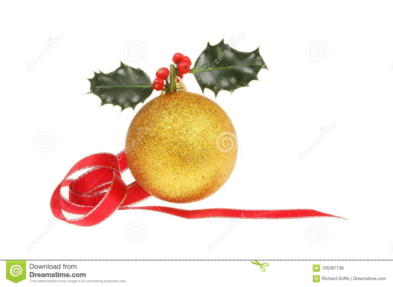 1f5cf74317ad Christmas decoration, gold glitter bauble with holly and a coiled red  ribbon isolated against white