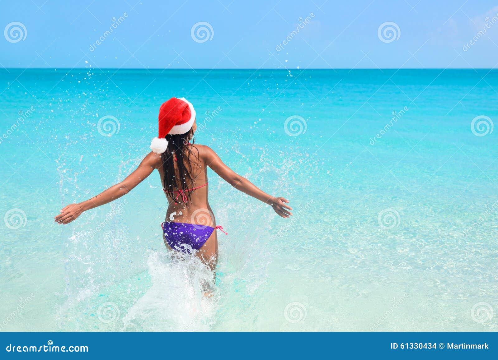 Christmas beach bikini woman swimming in ocean