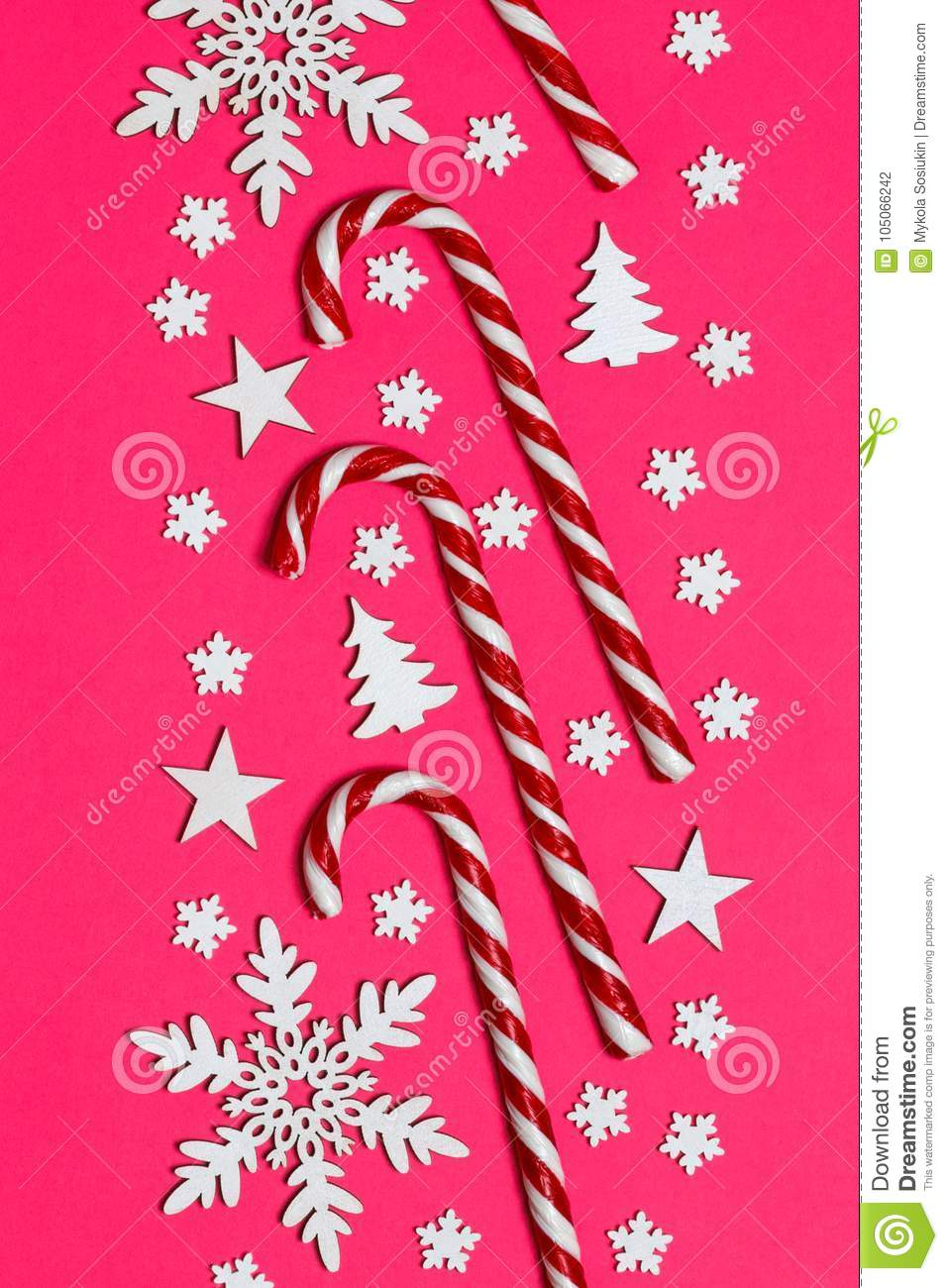 Christmas candy cane lied evenly in row on pink background with decorative snowflake and star. Flat lay and top view