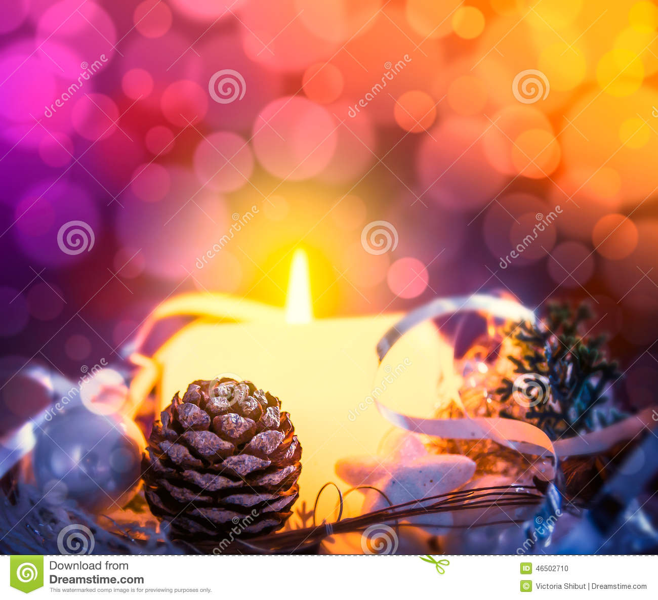 Christmas card with candle, spruce buds and scenery on bokeh