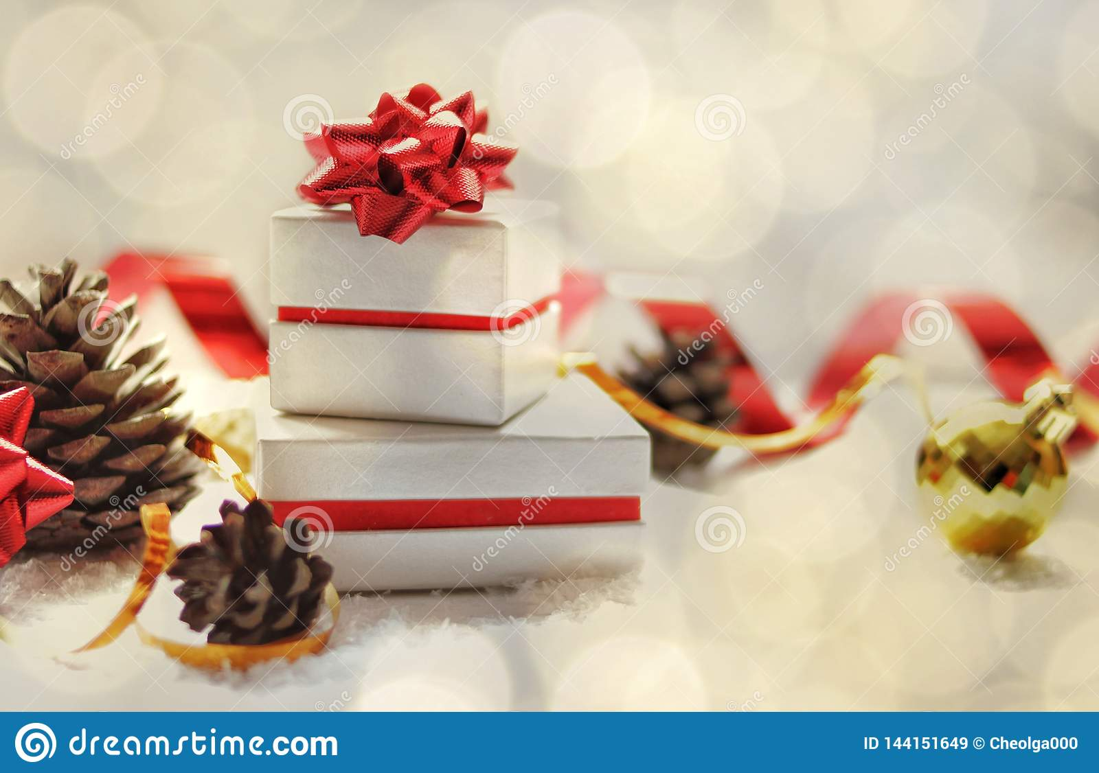 Christmas card. Christmas gift boxes with a red bow, Christmas ball, red ribbon, cones on a white background with snow and lights