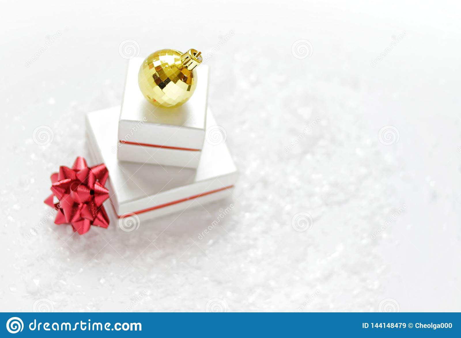 Christmas card. Christmas gift boxes with a red bow, golden Christmas ball, on a white background with snow