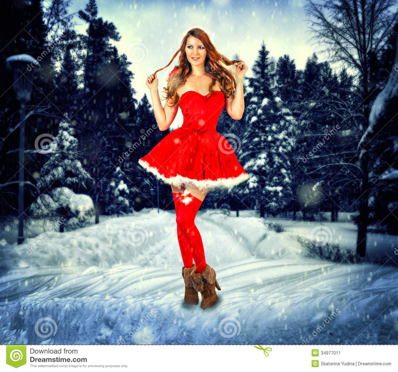 sexy woman wearing santa claus clothes stay in the snow forest