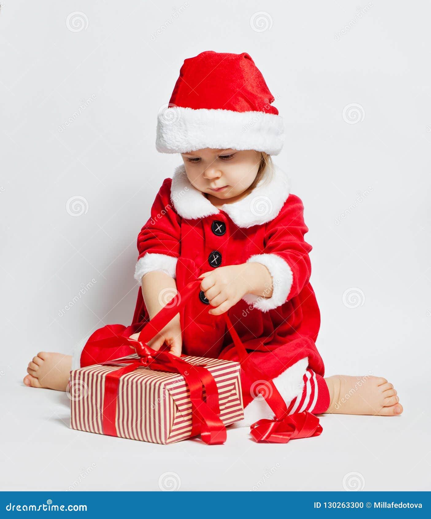 d4cb0441dbb Christmas Child Girl In Santa Hat Opening Xmas Gift Box Stock Photo ...