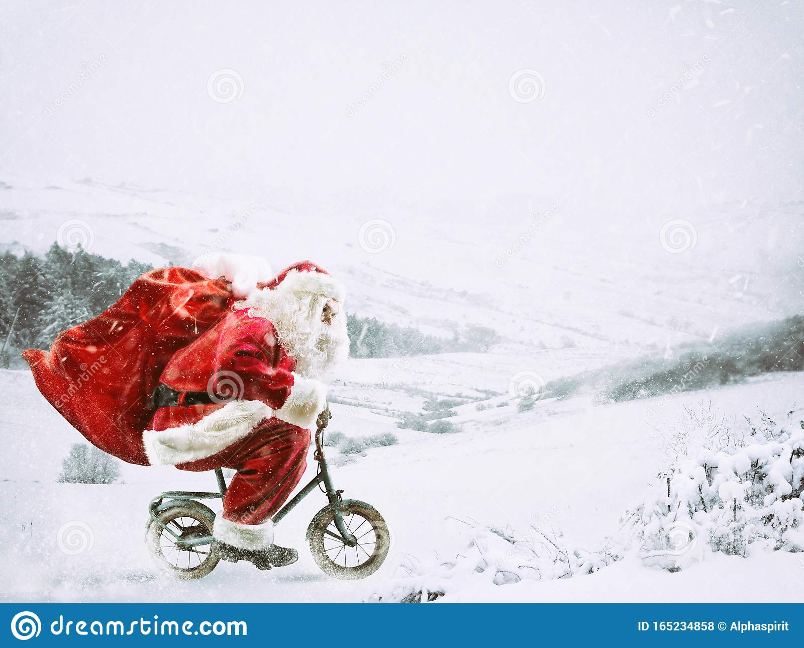 Santa Claus on a little bike on a winter landscape under the snow