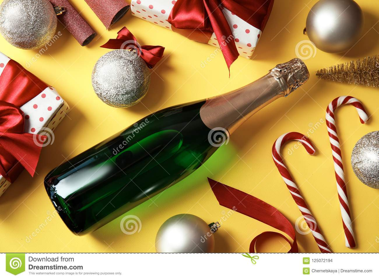 Christmas composition with bottle of champagne and gifts on color background