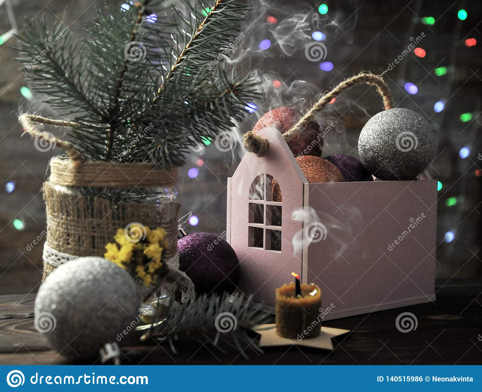 Christmas composition with a candle, a house and Christmas decorations on a table