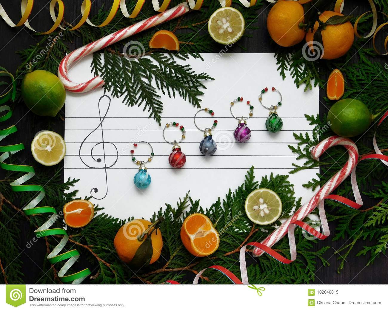 Christmas composition. Christmas decoration balls are arranged on the paper like music notes