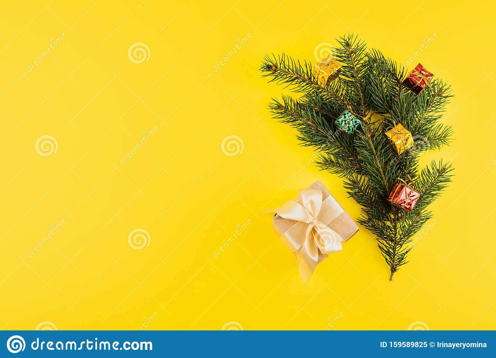 Christmas composition with Conifer Evergreen tree branches and gift box on yellow background. Christmas and 2020 new year minimal