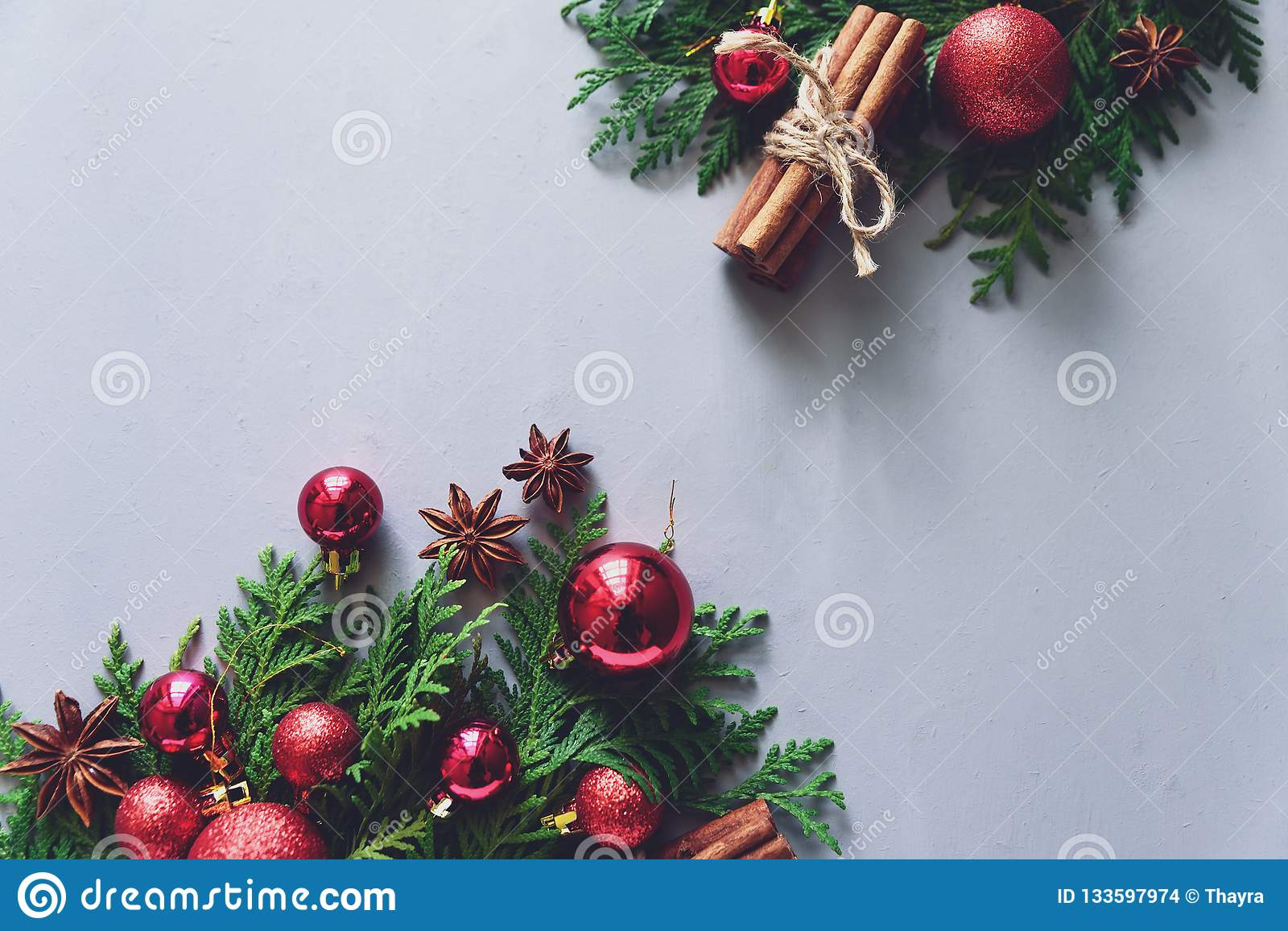 Christmas composition. Christmas fir tree branches, balls, cinnamon sticks and anise stars on gray wooden background. Flat lay. To