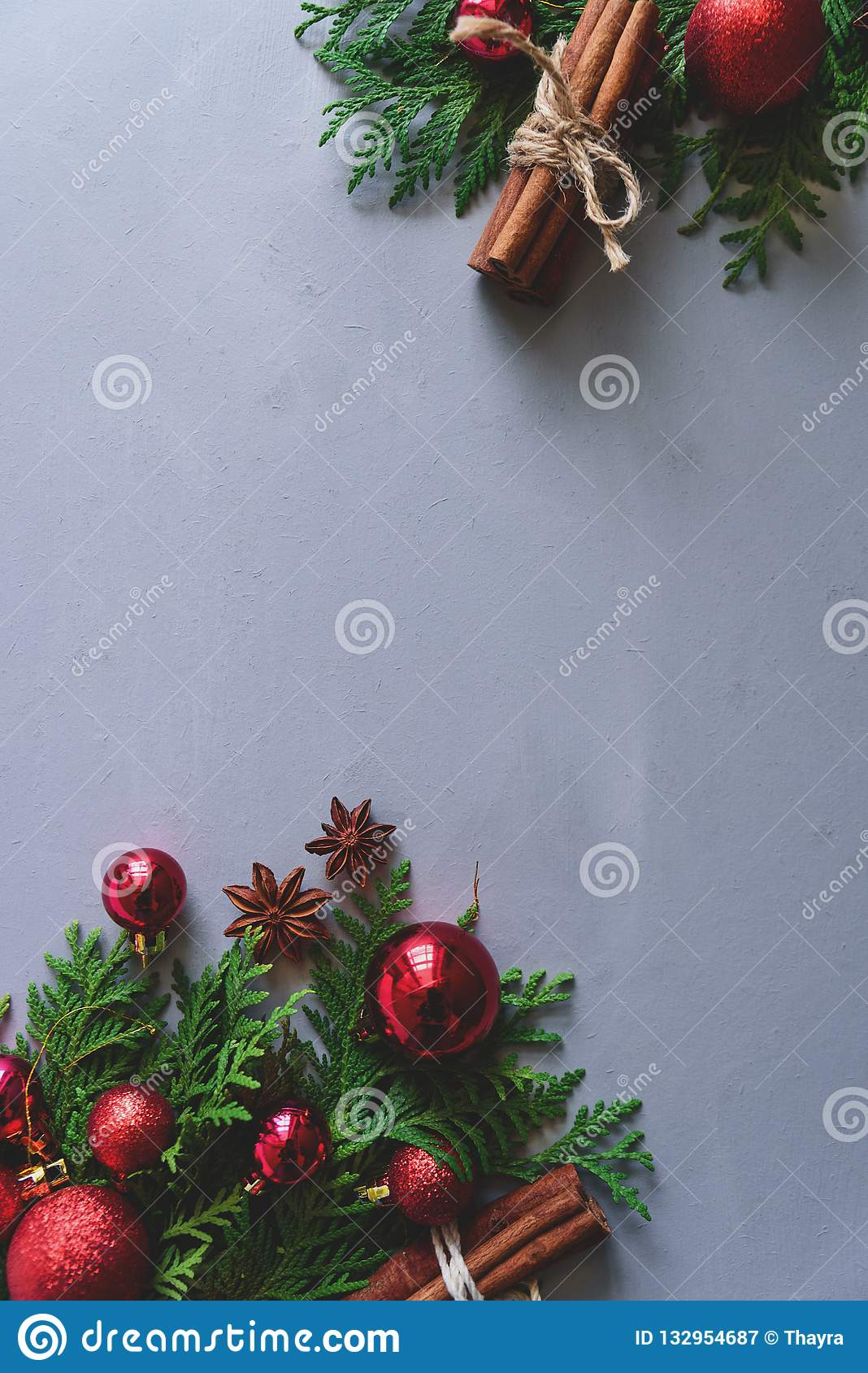 Christmas composition. Christmas fir tree branches, balls, cinnamon sticks and anise stars on gray wooden background. Flat lay.