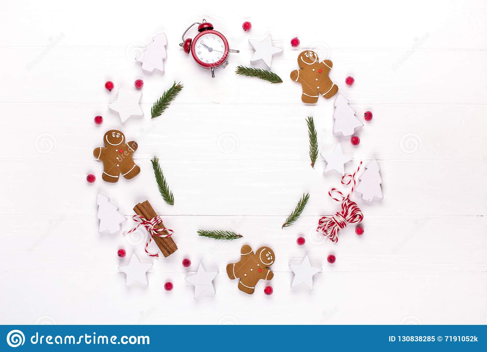 Christmas composition. Round frame made of decorations, fir tree branches, gingerbread man cookies on white background. Winter ho