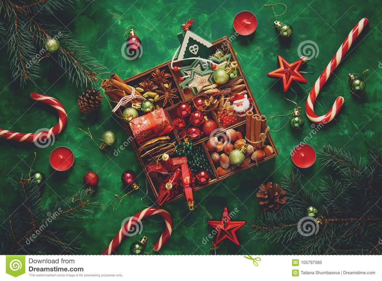 Christmas composition. Christmas tree and box with spices and toys on green wooden background