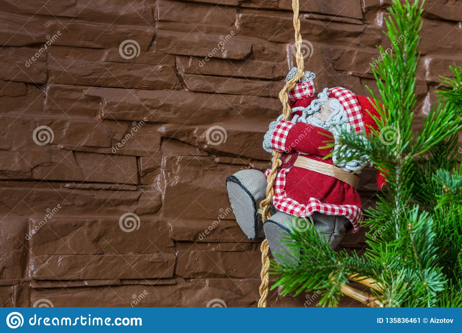 Christmas composition of a Christmas tree and Santa Claus climbing a rope