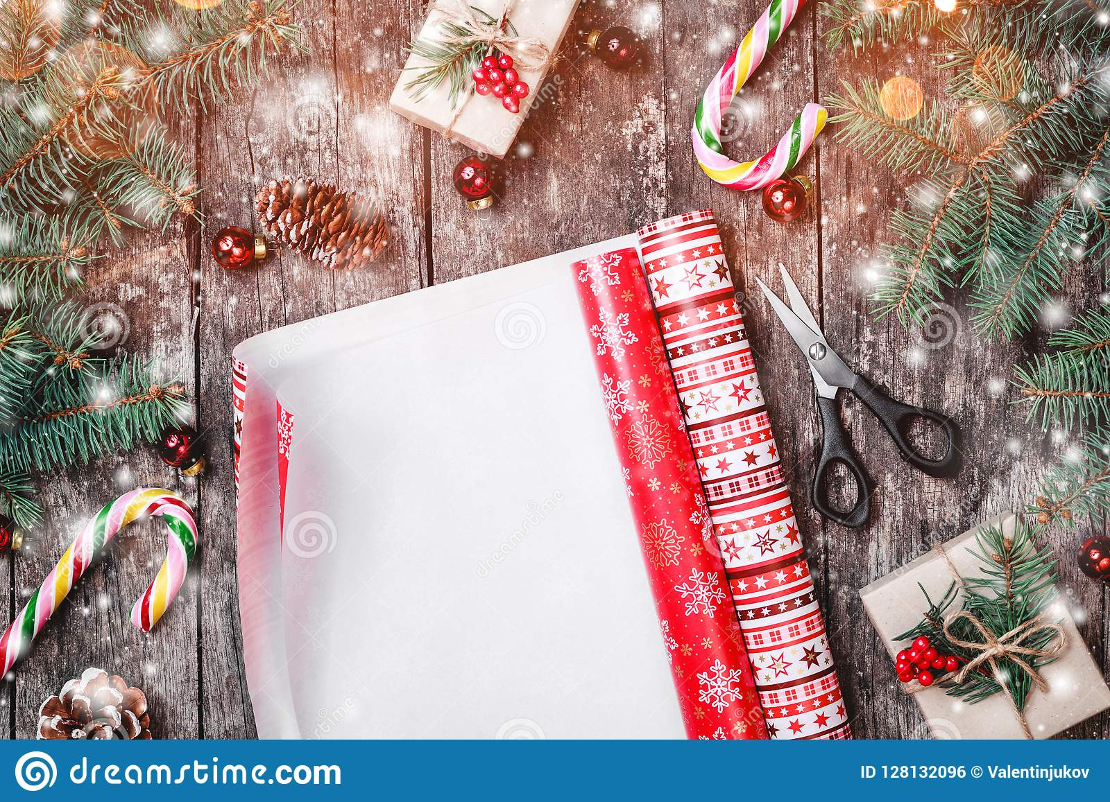 Christmas composition with xmas wrapping, Fir branches, gifts, pine cones, red decorations on wooden background.