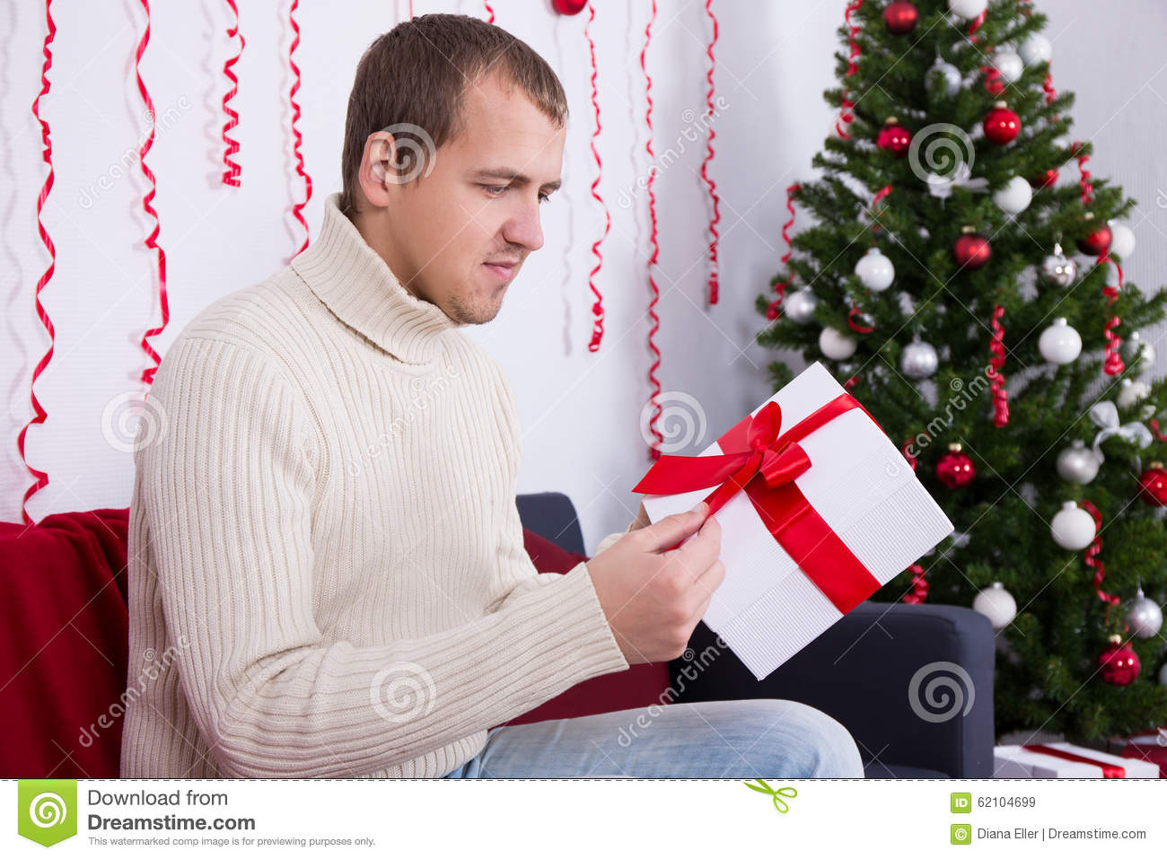 christmas concept - happy young handsome man opening gift in living room