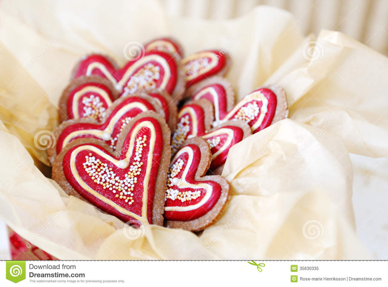 Heart shaped gingerbread cookies decorated in red and gold