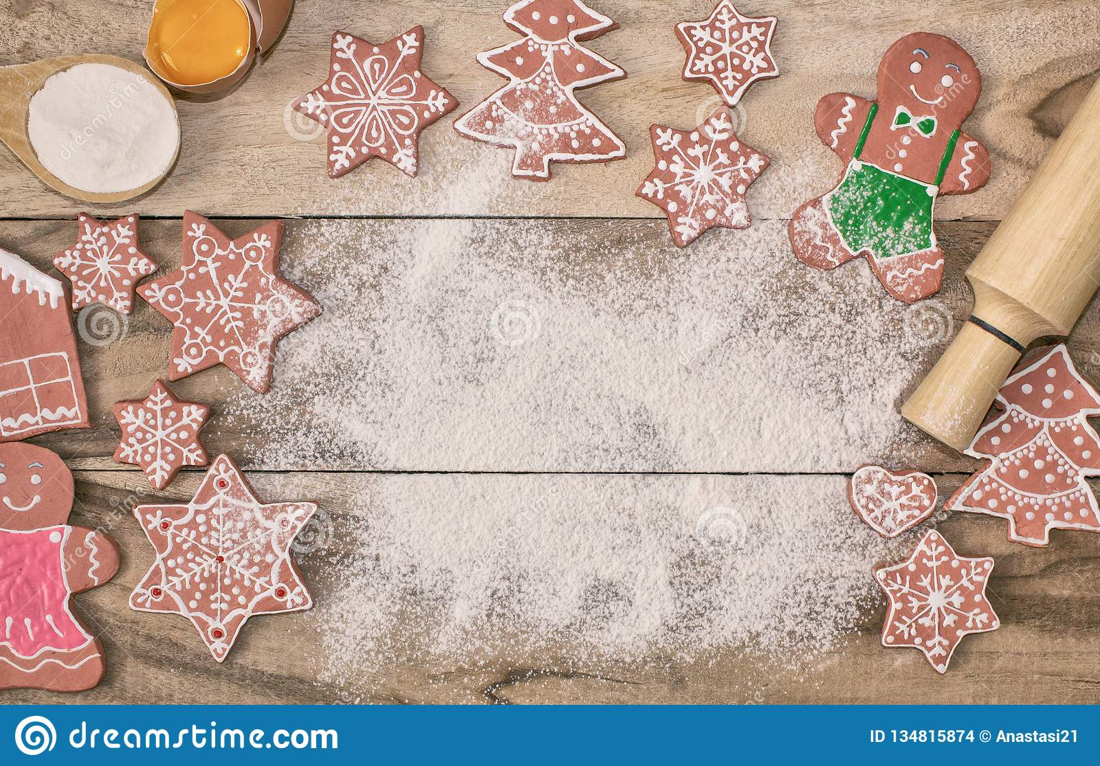 Christmas cooking. Flour for baking, eggs, ginger biscuits and Gingerbread man on wooden background. With free space for text.