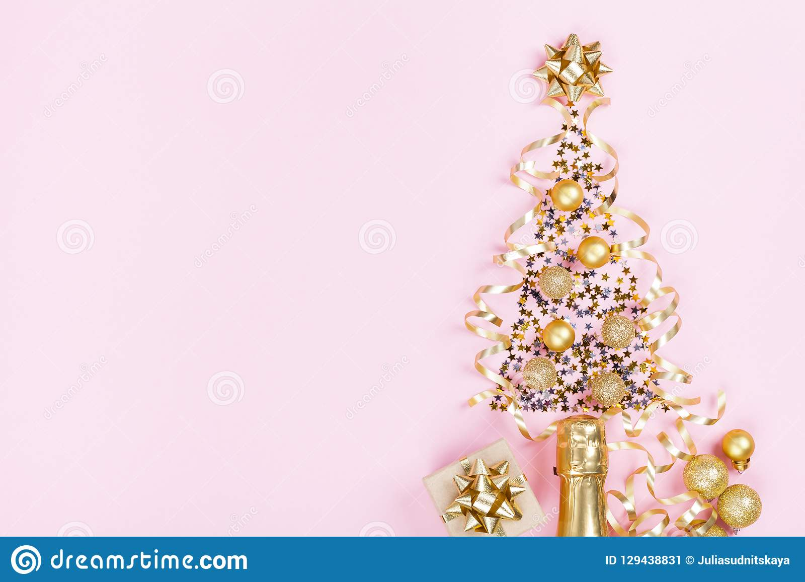 Christmas creative fir tree from champagne, confetti stars and serpentine with gift box on pink background top view. Flat lay.