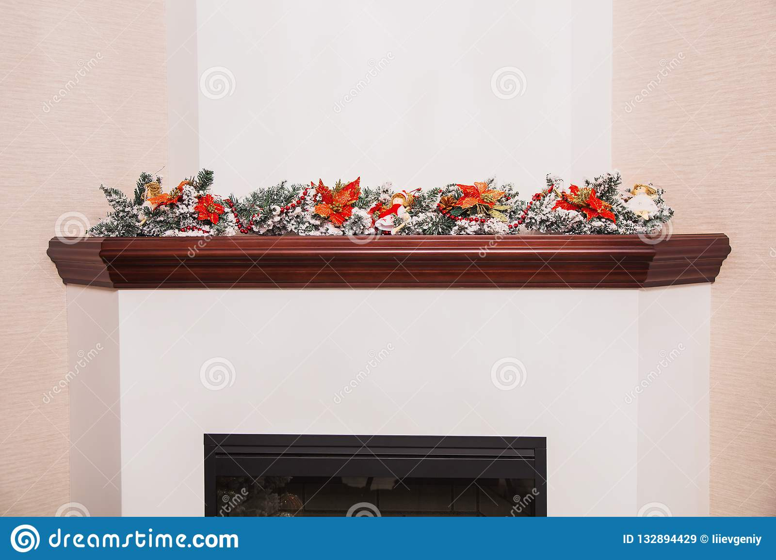 Christmas decor in the house. Winter tree with smow. New Year decorations on fireplace. Branch of spruce with snow. Christmas post