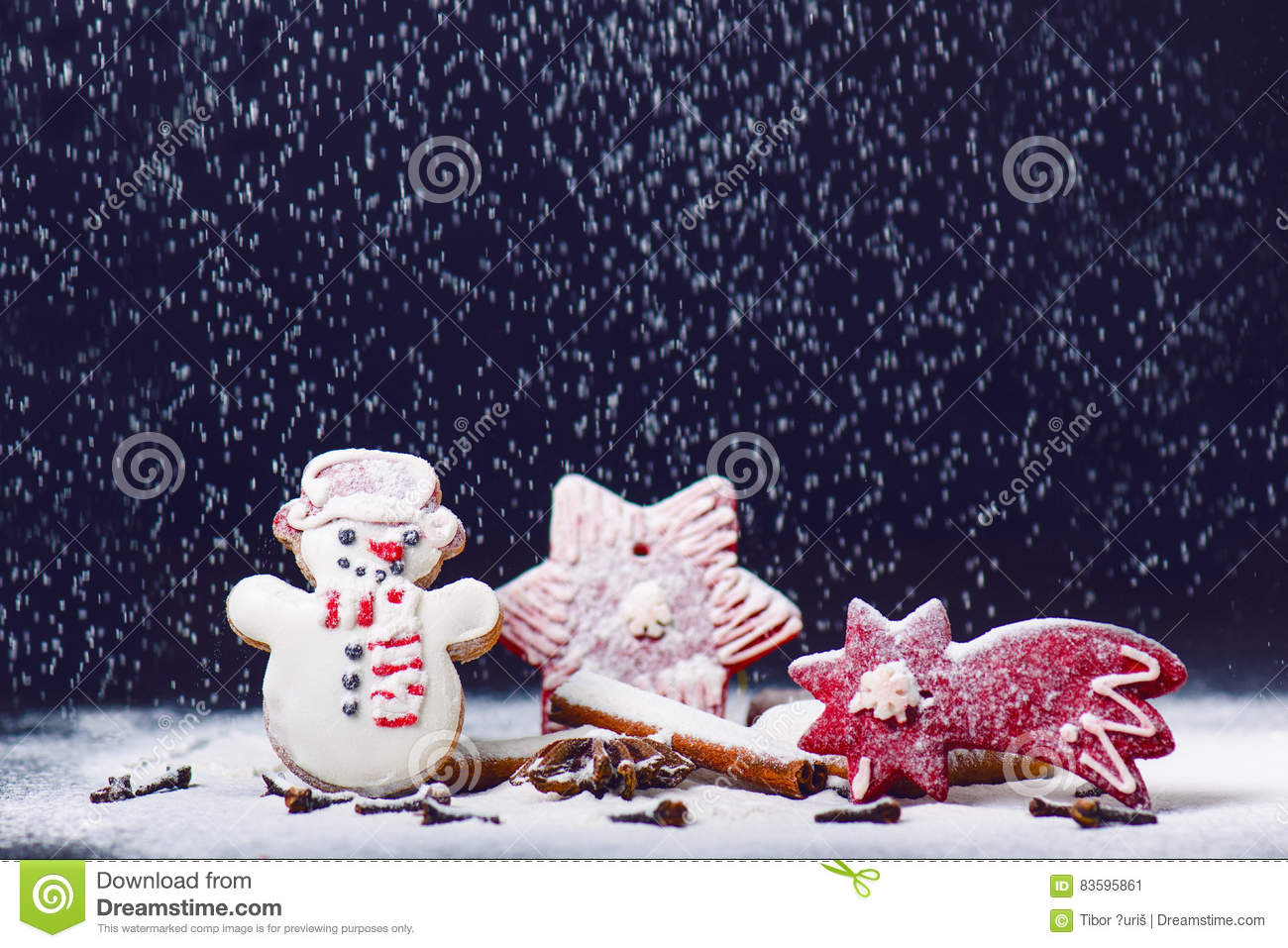 Christmas decoration and cookies.Woman hand sprinkling sugar on a cookies. Flour and spices for a baking on a dark backg