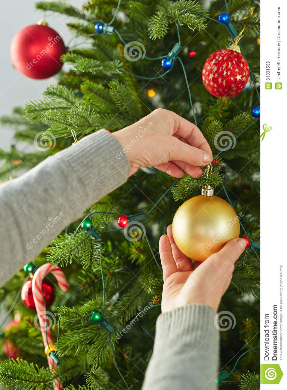 Human hand holding toy bubble on branch of decorated christmas tree
