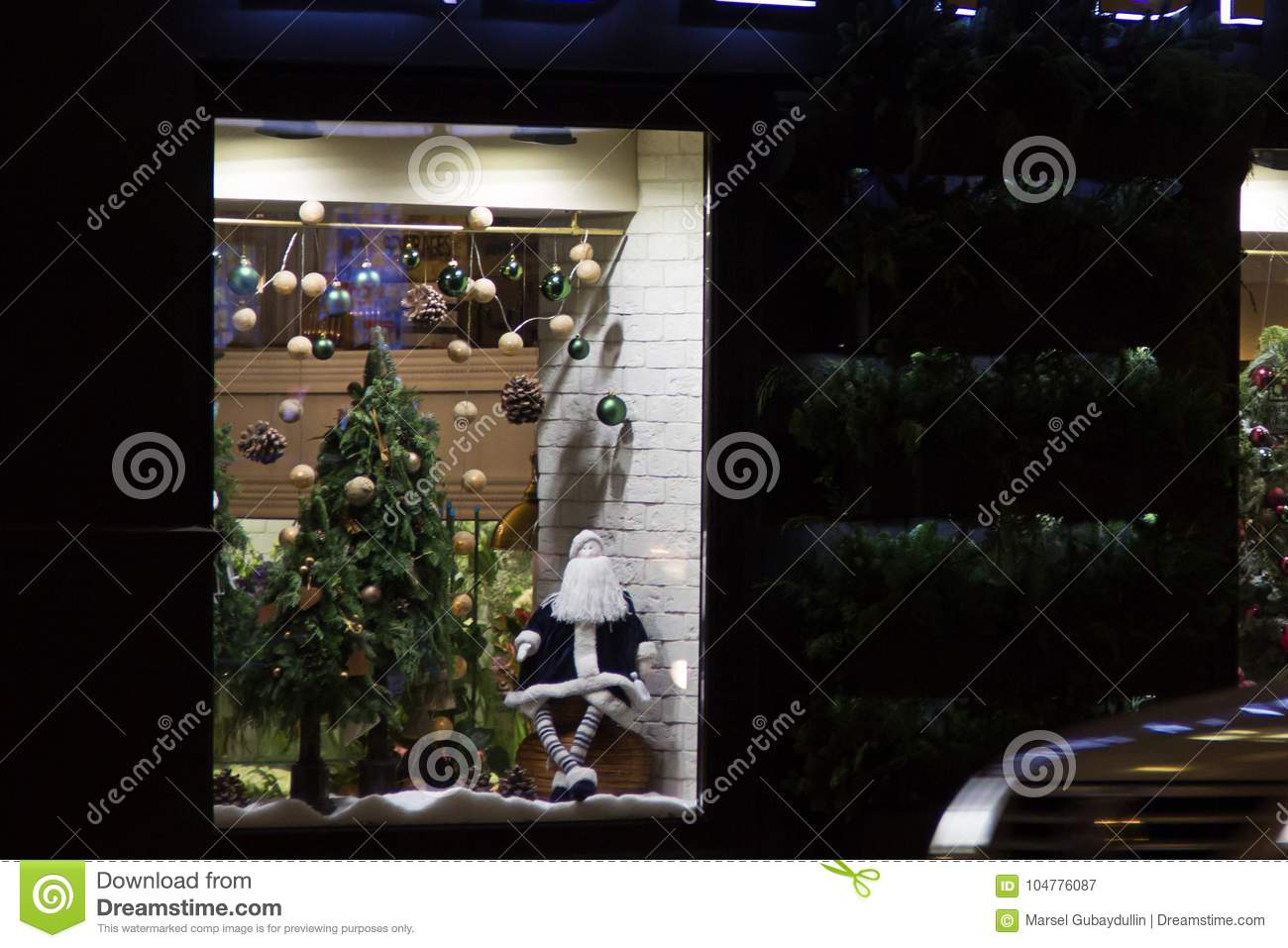 Christmas decoration on a shop window. Santa claus doll, christmas tree with glass balls and pinecones