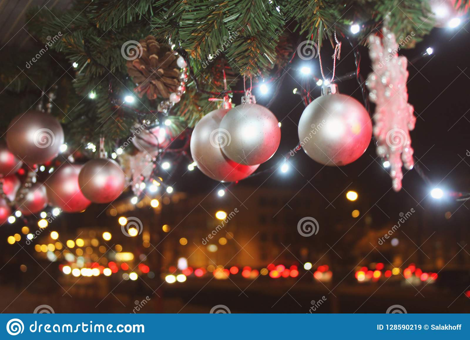 Christmas decoration with a silver toy in the form of balls on the blurry background of night city lights.