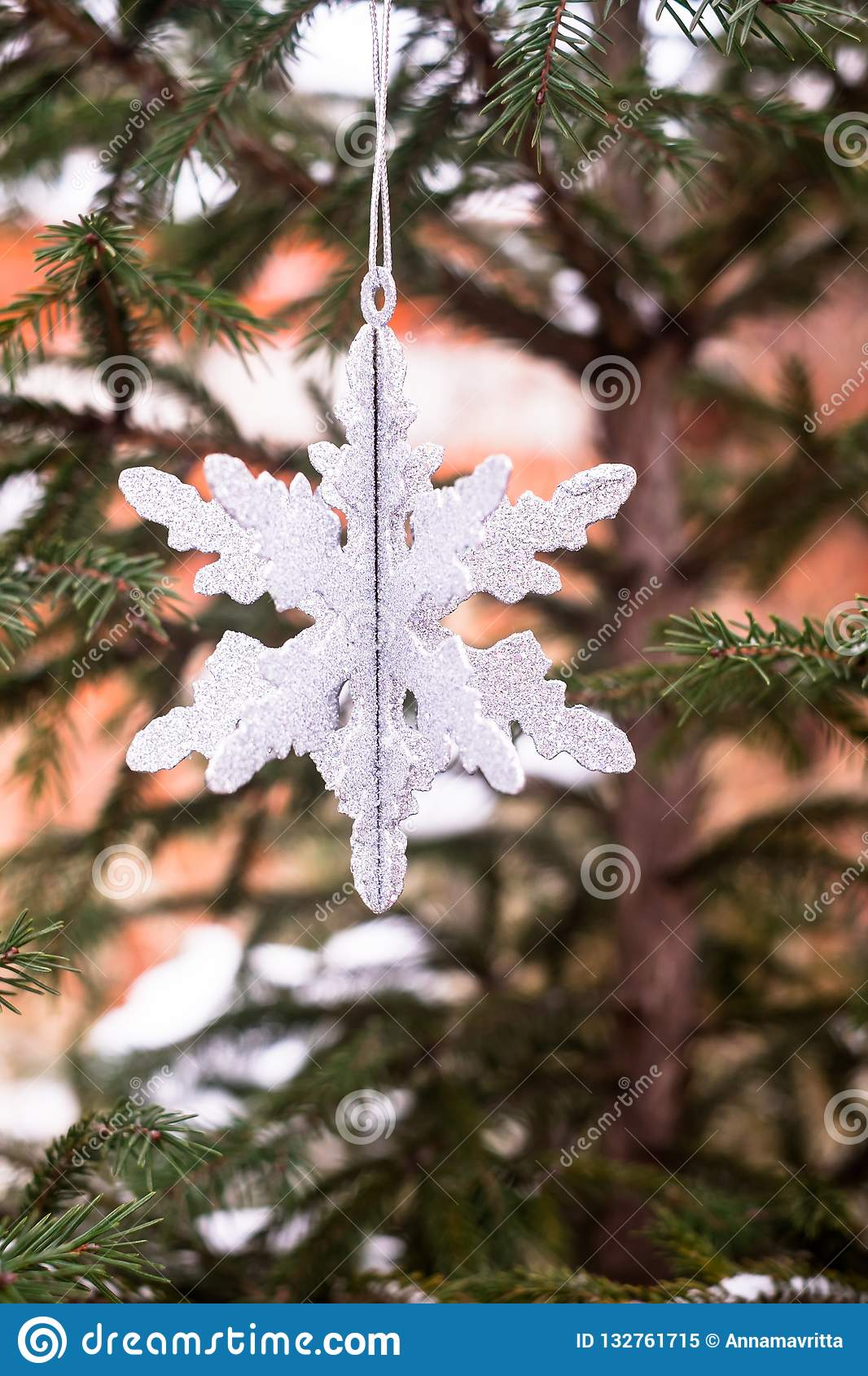 Christmas decoration with a toy in the shape of silver snowflake, selective focus. Image with copy space.