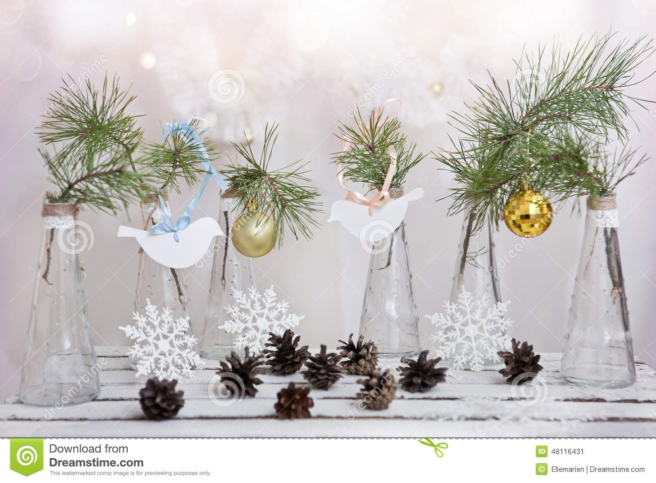 christmas decorations on a branch of tree in glass vases