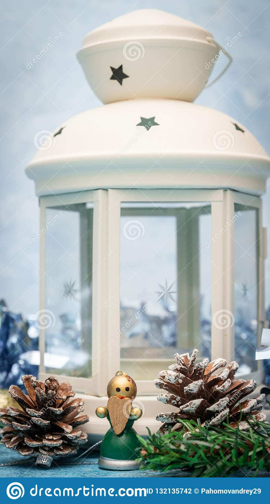 Christmas decorations. Candlestick candle close-up with a small wooden angel with a heart in his hands
