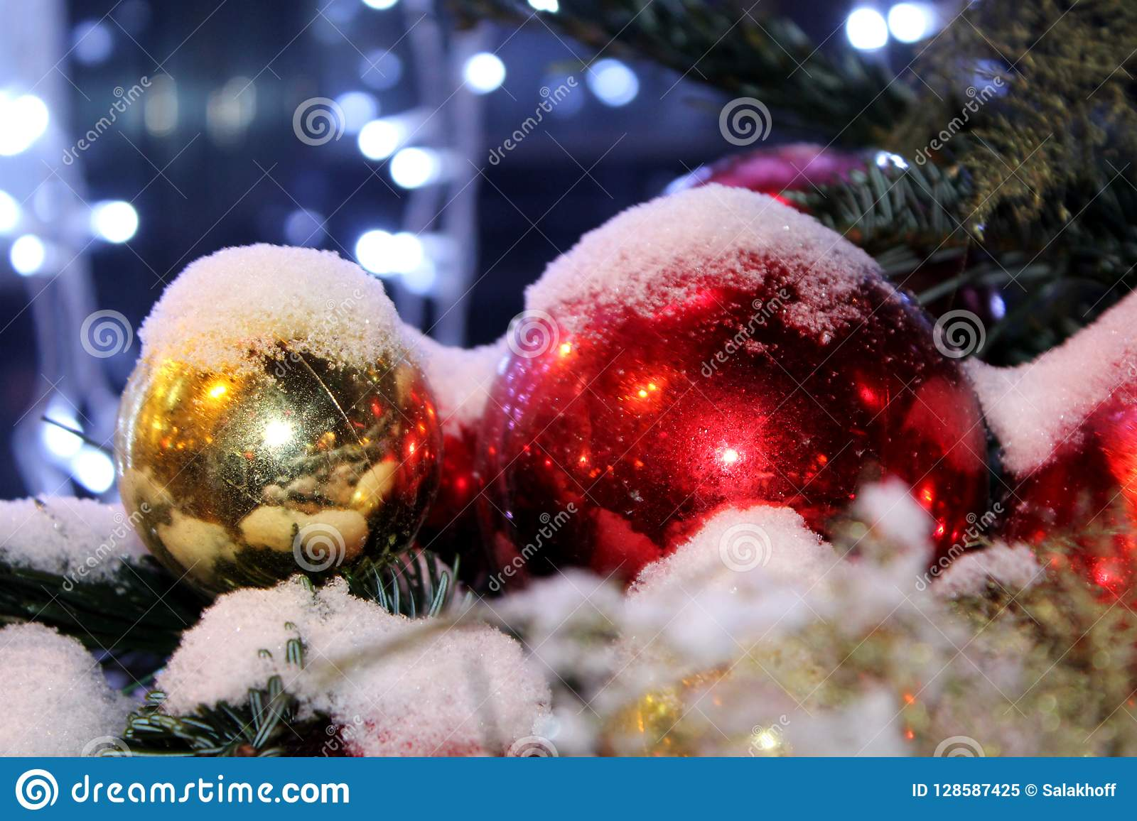 Christmas decorations on the Christmas tree in red and gold colors strewn with lights, close-up.