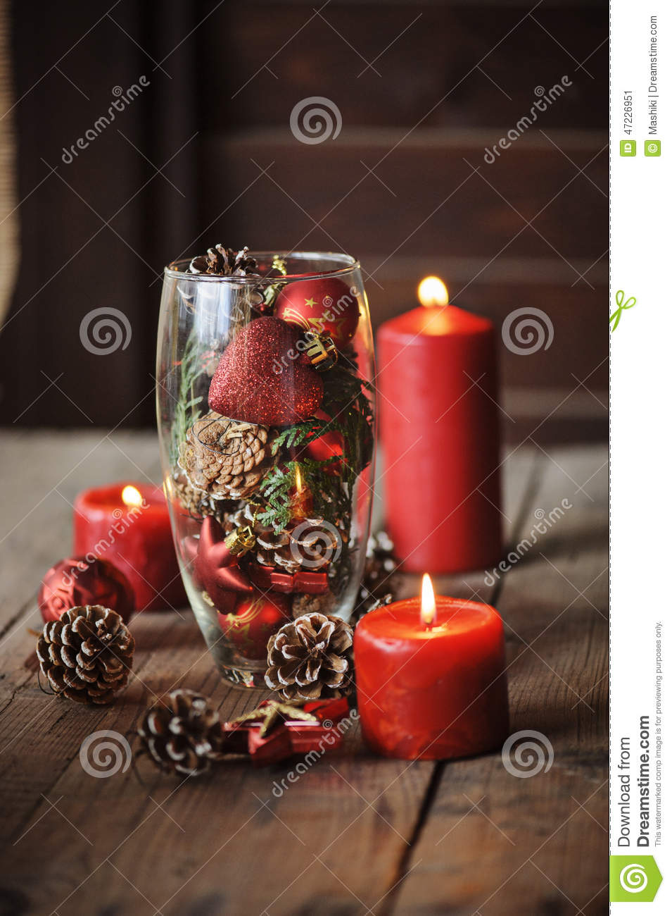 christmas decorations and pine cones in glass vase