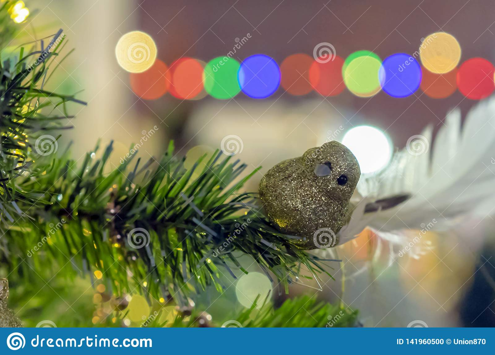 Christmas decorations. A shiny golden bird on a branch of a Christmas tree