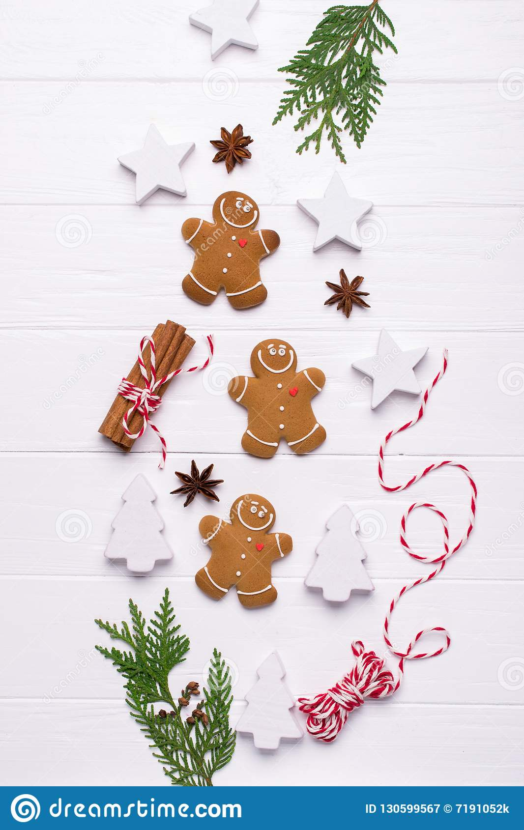 Christmas Decorative Border made of Festive Elements. Smiling gingerbread man, christmas white decorations, pine branches.