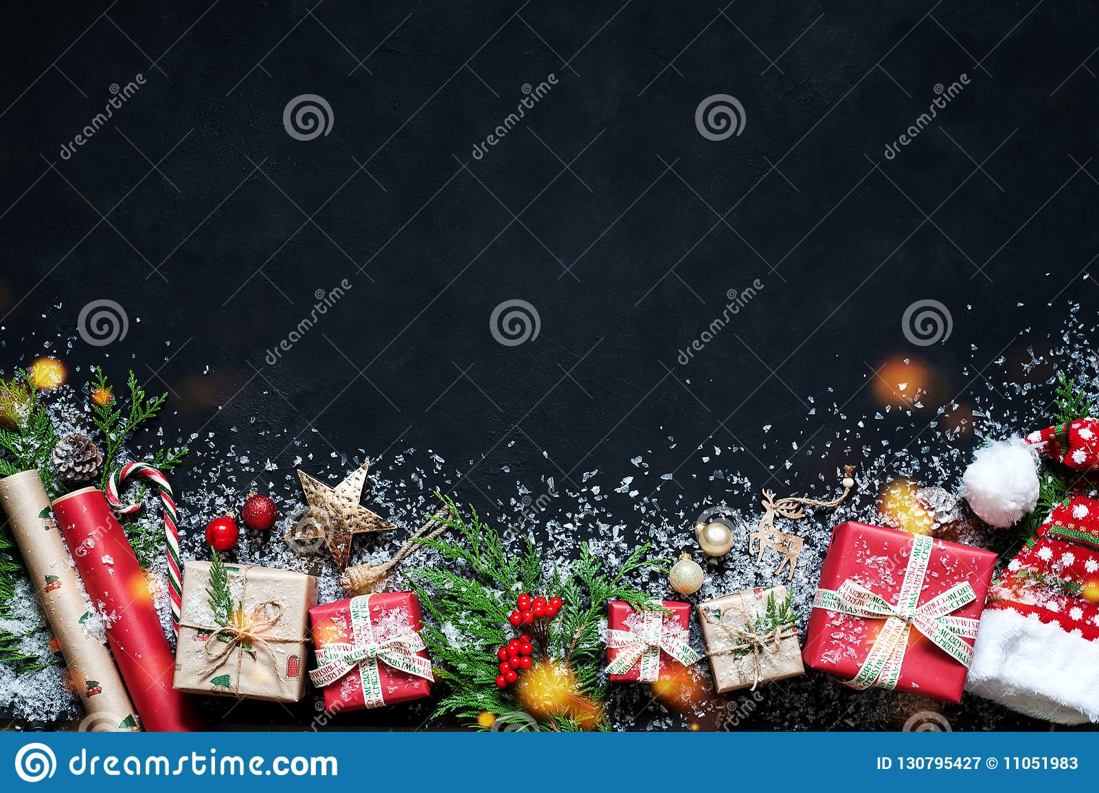 Christmas composition on a black background Christmas decorations, boxes, branches of tree, cap, Santa, star.