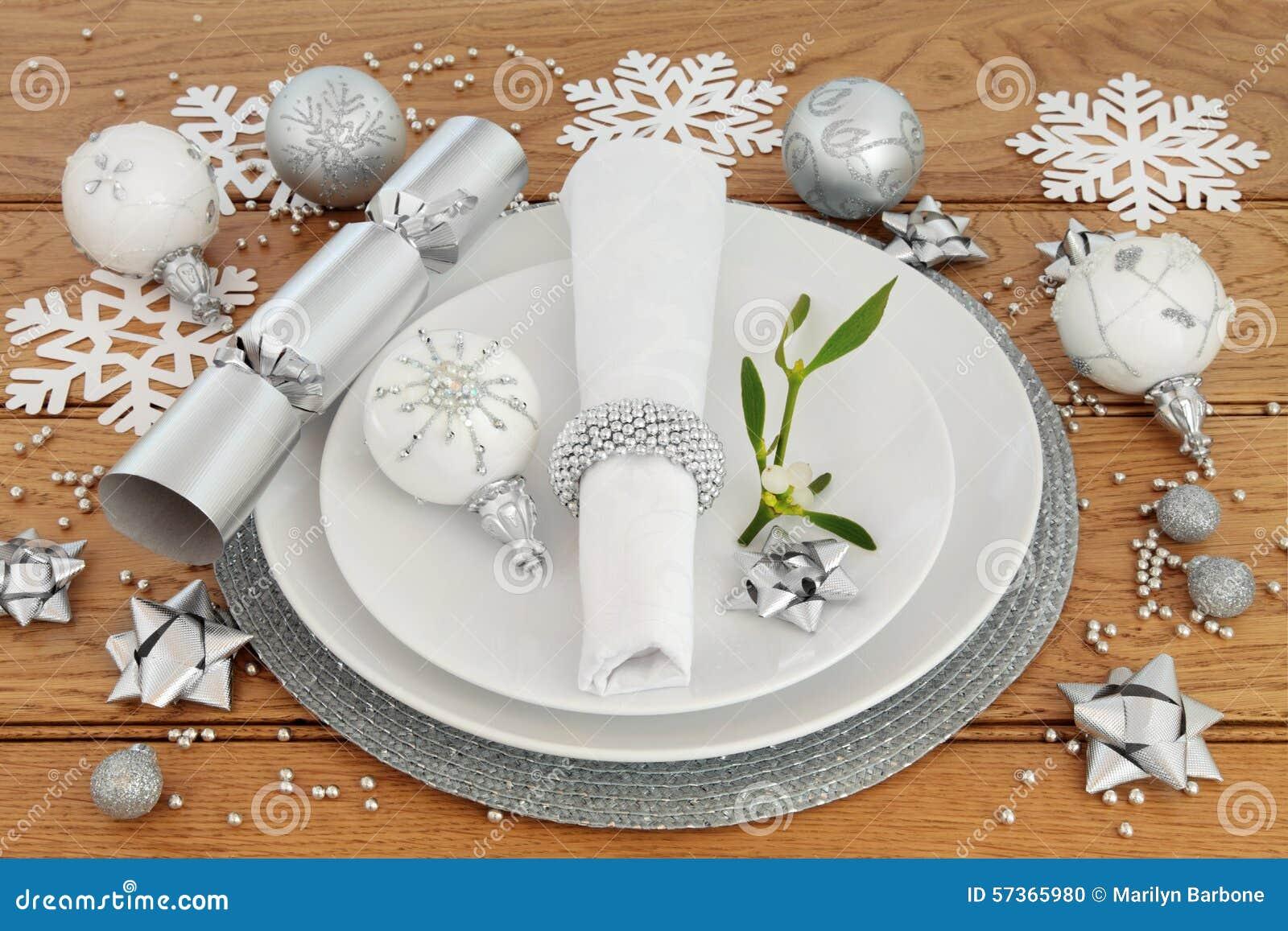 ... plates, napkin, bauble decorations, mistletoe over oak background