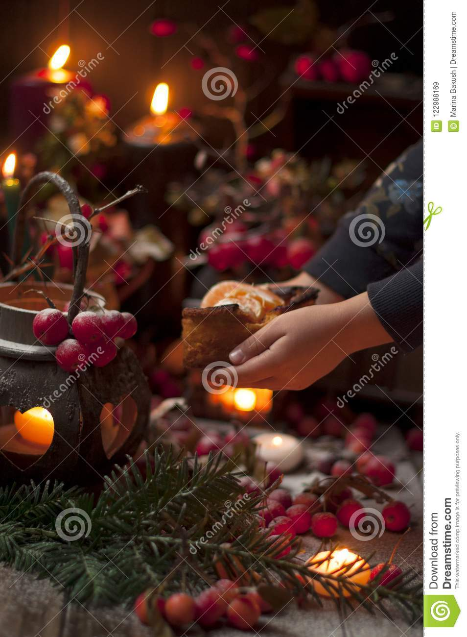 A Christmas fairy tale with candles and berries under the snow. Little girl and christmas decor.