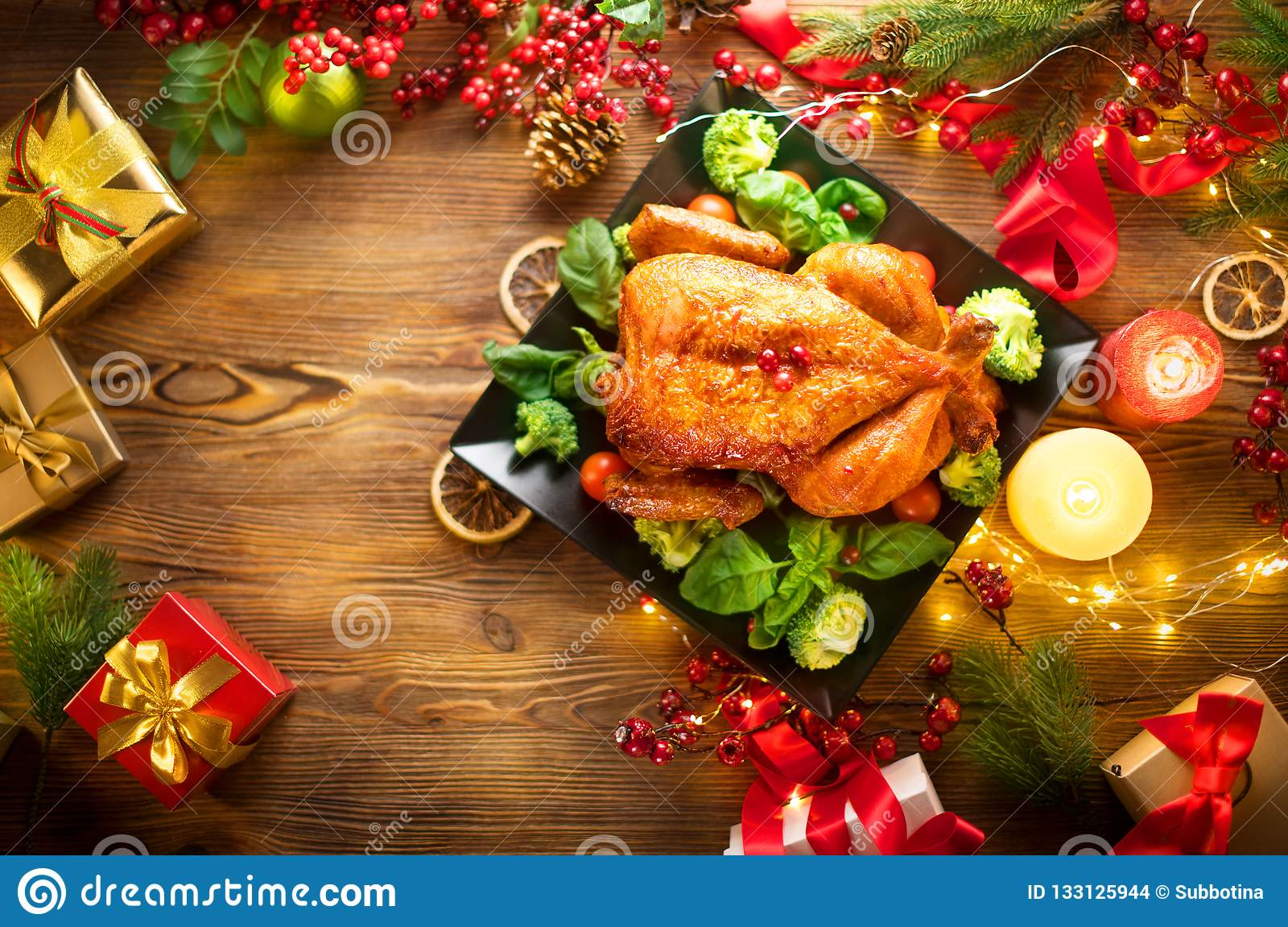 Christmas family dinner. Roasted chicken on holiday table, decorated with gift boxes, burning candles and garlands