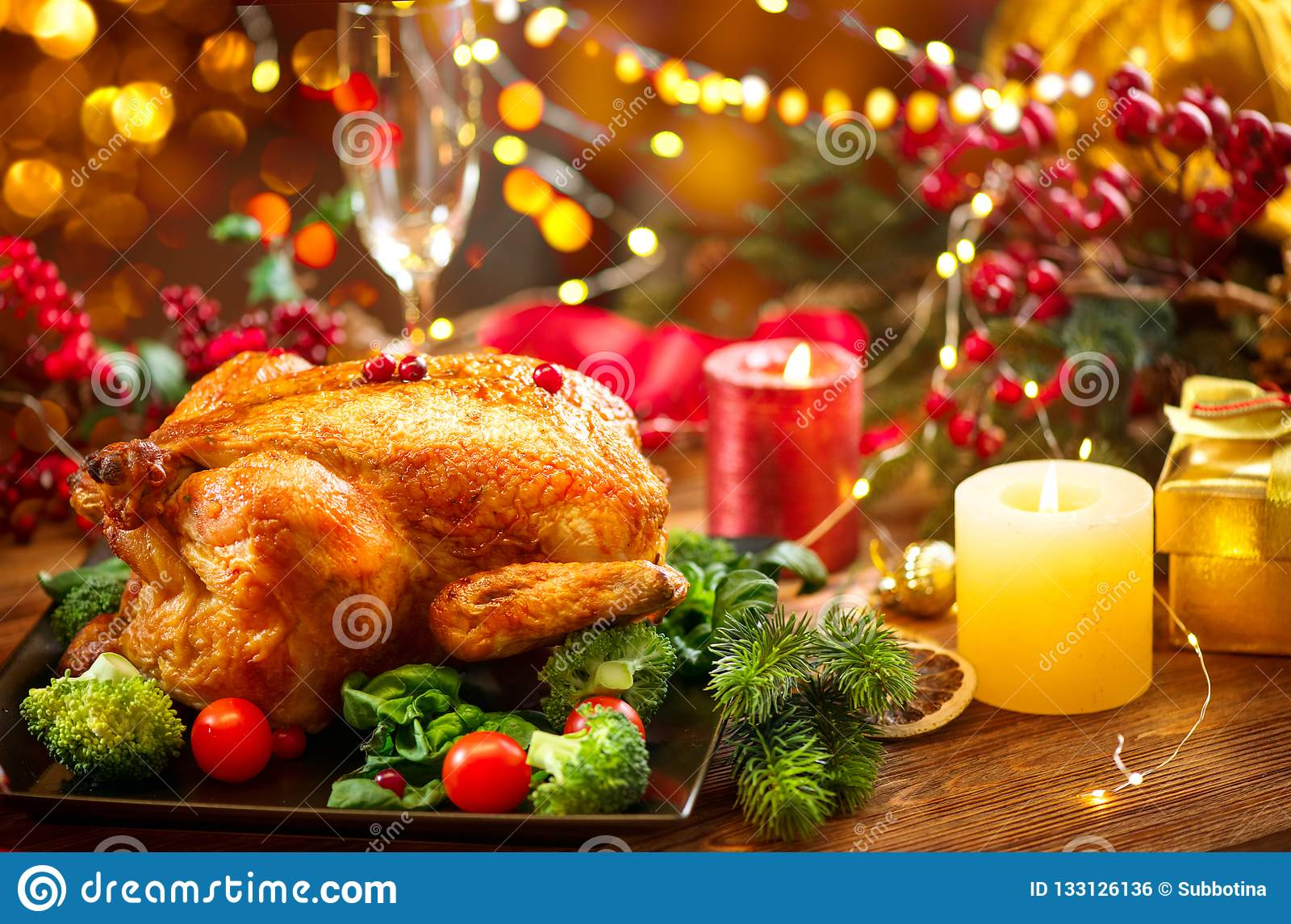 Christmas family dinner. Roasted chicken on holiday table, decorated with gift boxes, burning candles and garlands. Roasted turkey
