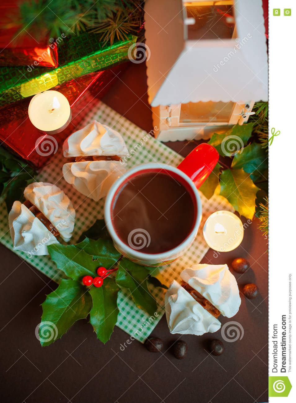 Christmas festive composition - a mug with Santa Klais, cakes, candles, branches of holly, berries and boxes gifts on