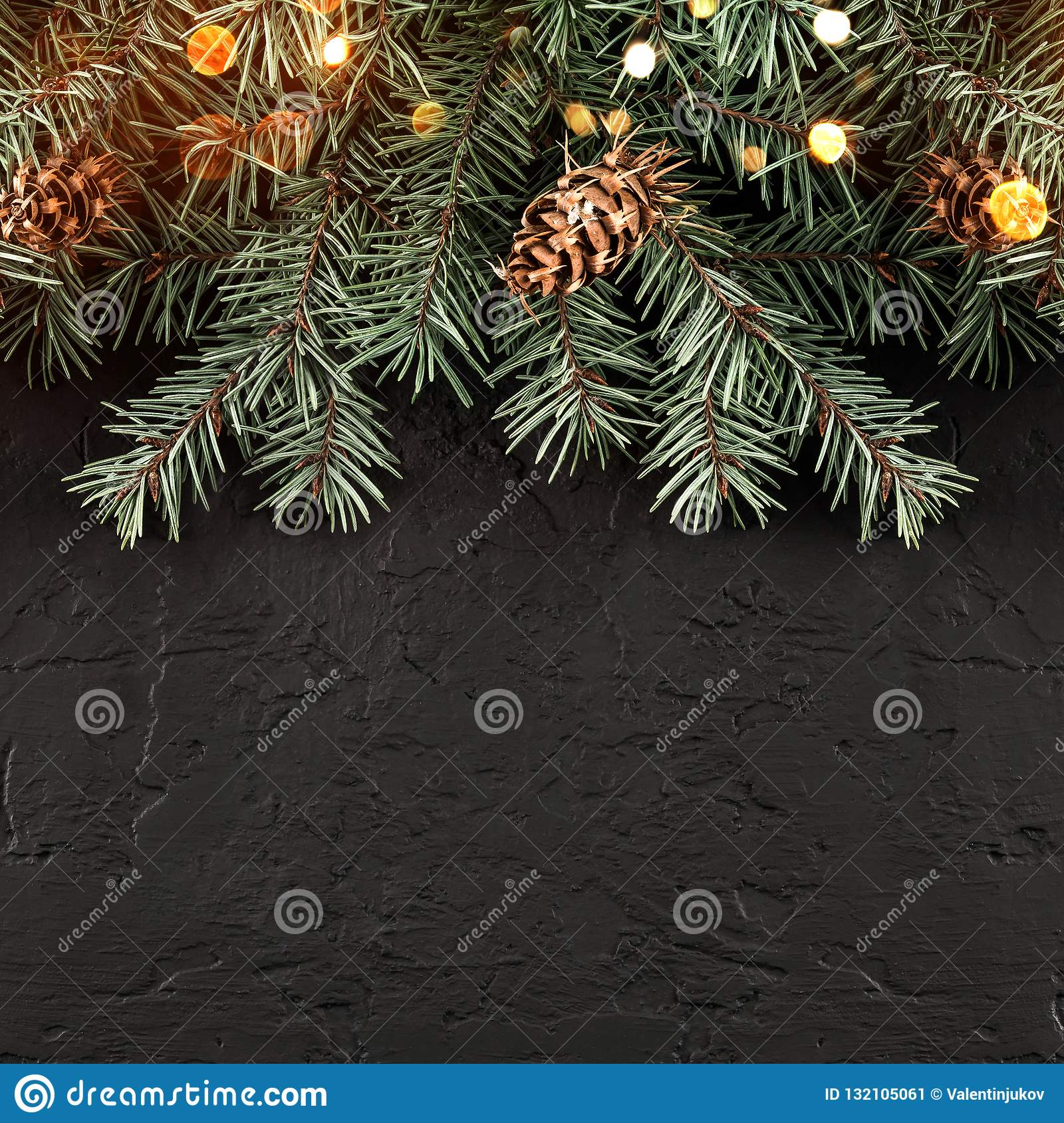 Christmas Fir branches with lights on dark black background. Xmas and Happy New Year card, bokeh, sparking, glowing.