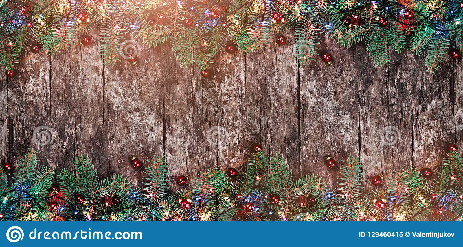Christmas Fir branches with lights and red decorations on wooden background. Xmas and Happy New Year frame.
