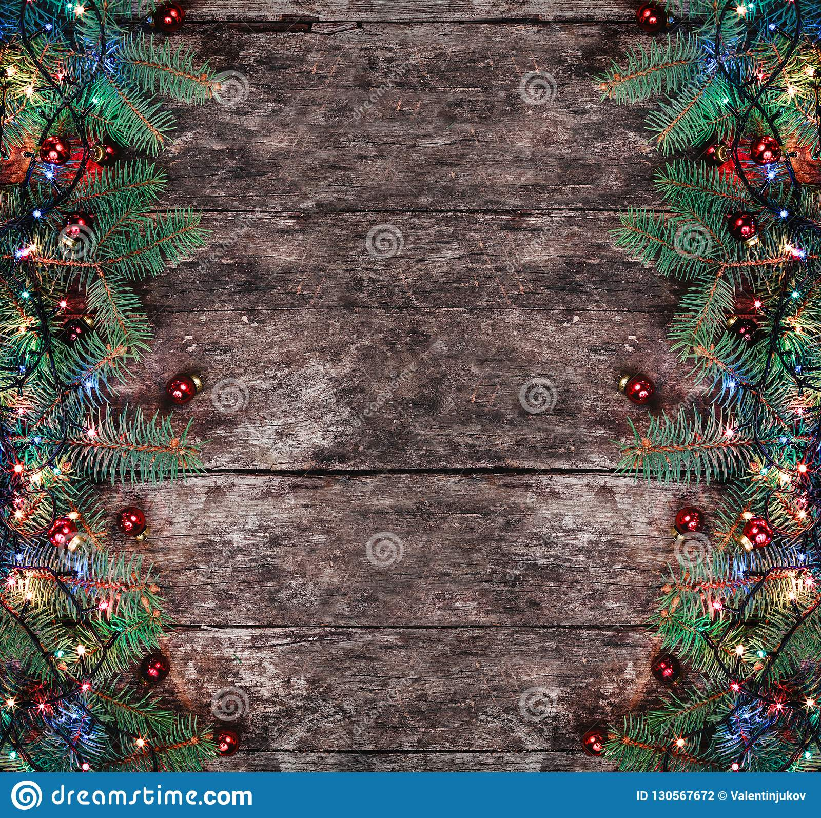 Christmas Fir branches with lights and red decorations on wooden background. Xmas and Happy New Year composition