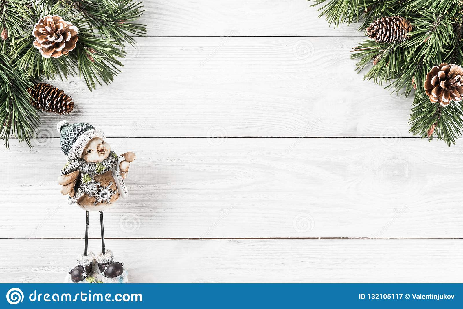 Christmas fir branches with pine cones and Christmas decoration on white wooden background. Xmas and Happy New Year theme.