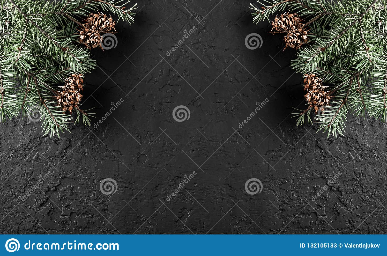 Christmas Fir branches with pine cones on dark holiday background with light. Xmas and Happy New Year theme.