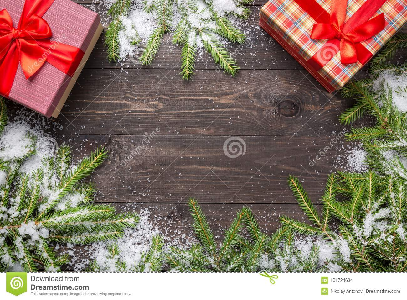 Christmas fir tree branches on a dark wooden board with snow and gift-boxes. Christmas or new year frame for your project with cop