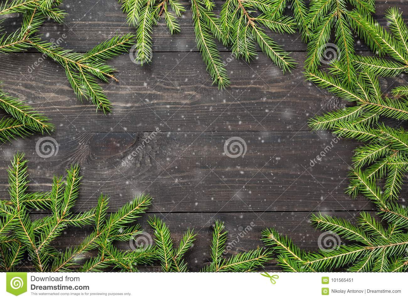 Christmas fir tree on a dark wooden board with snow. Christmas or new year frame for your project with copy space.