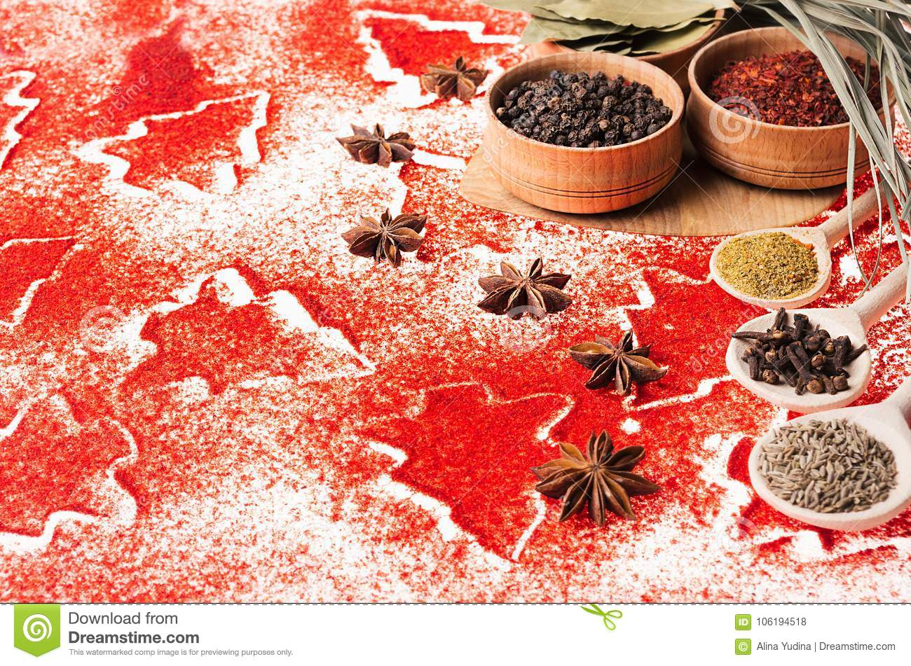 Christmas food background - different dry spices in wooden bowls on red christmas trees pattern, closeup, copy space.