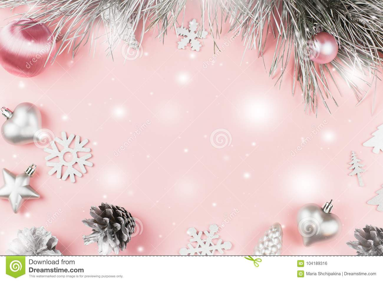 Christmas frame with fir branches, conifer cones, christmas balls and silver ornaments on pastel pink background